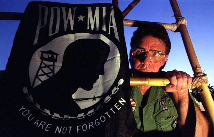 Vietnam War veteran Bob Kakuk helped lead the fight for government buildings to display the flag of prisoners of war and the missing. Kakuk poses with the flag and a model of a POW bamboo cage which he uses to dramatize the cause.