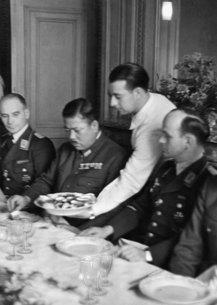 Japanese General Tomoyuki Yamashita seated between German officers during his visit to the 53rd German Bomber Wing near Calais, France, as part of his covert tour of Nazi military operations in World War II.