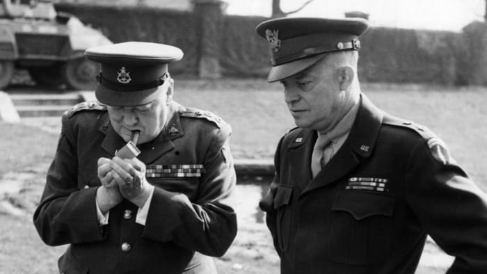 Prime Minister Winston Churchill lights a cigar during his stay at Allied headquarters in France with American General Eisenhower, March 1945.