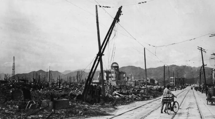 A man rides his bicycle through Hiroshima, days after the city was razed to the ground by an atomic bomb explosion, in Japan. The view here is west-northwest, about 550 feet from where the bomb landed, known as the X, on August 6, 1945.