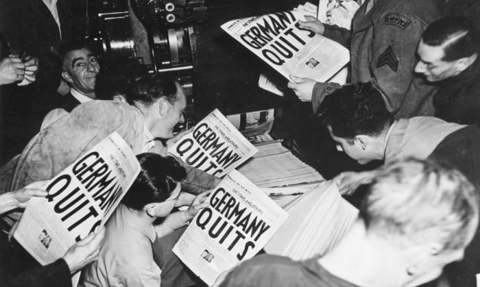 Allied soldiers and others read copies of the Stars and Stripes military newspaper, owned by the London Times, which announces Germany's surrender during World War II on May 7, 1945.