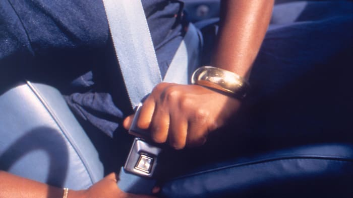 A person who fastens his seat belt in a motor vehicle;  image courtesy CDC, 1990.