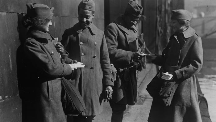 Two soldiers from the 351st Field Artillery who returned to the 'Louisville' receive candy from the Salvation Army women who greet each troop ship arriving in port, 1919.