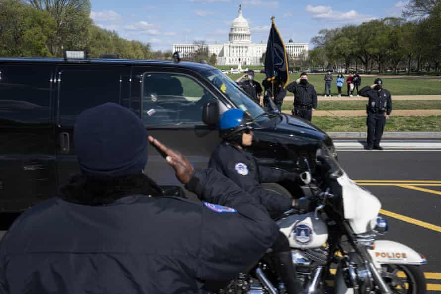 Capitol police officers salute as a procession carries the remains of the officer killed.