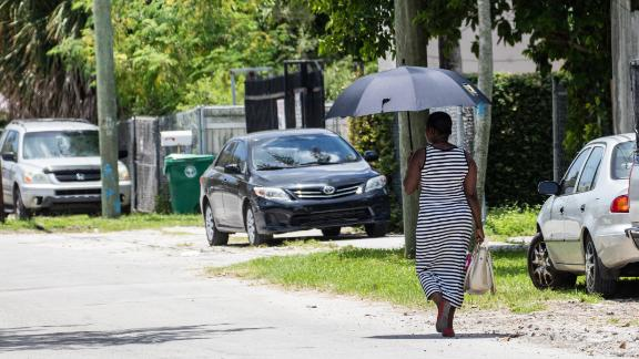 A woman uses an umbrella for shade on hot days, he walks in Miami.