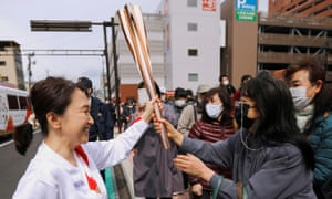 Spectators touch the torch carried by torchbearer Junko Ito, on the second day of the Olympic torch relay in Fukushima, Japan 26 March, 2021.