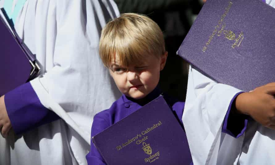 A choirboy looks on as dignitaries leave the cathedral
