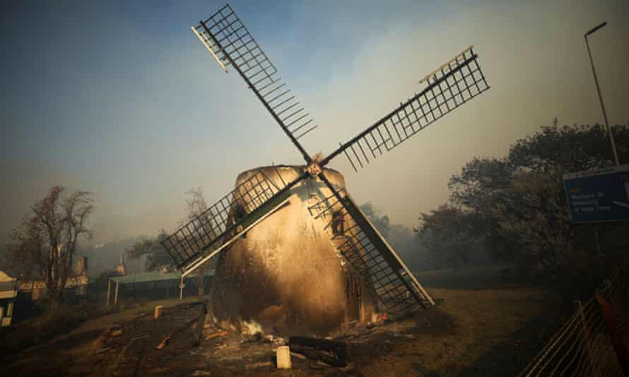 The historic Mostert's Mill smoulders as firefighters battle to contain a fire, in Cape Town