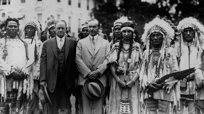 President Calvin Coolidge (right) stands on the South Lawn with Charles H. Burke, Commissioner of Indian Affairs, and members of the Blackfoot Tribe, c.  1927.