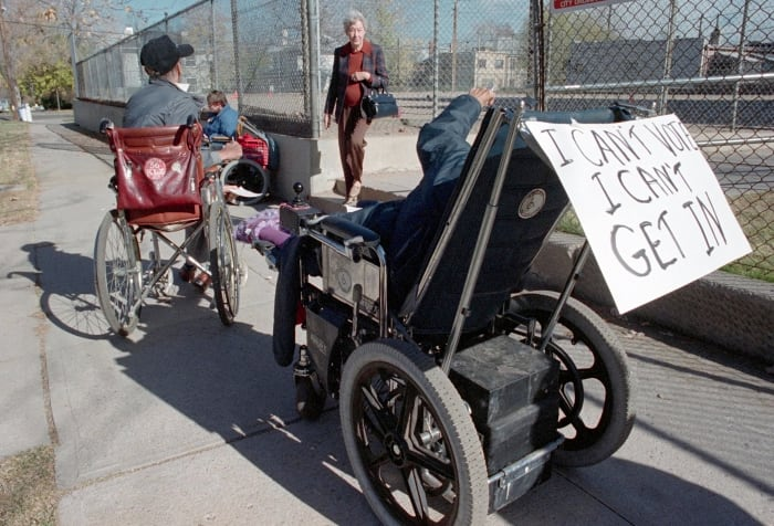 Protesters in wheelchairs surround an entrance to a Denver polling station to draw attention to the flights of stairs preventing them from reaching the voting booths, c.  1988.