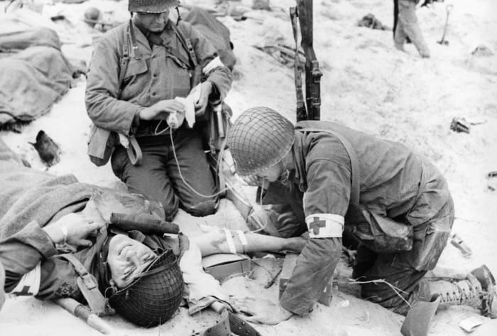 Doctors treating an injured soldier on D-Day administer a blood plasma transfusion.