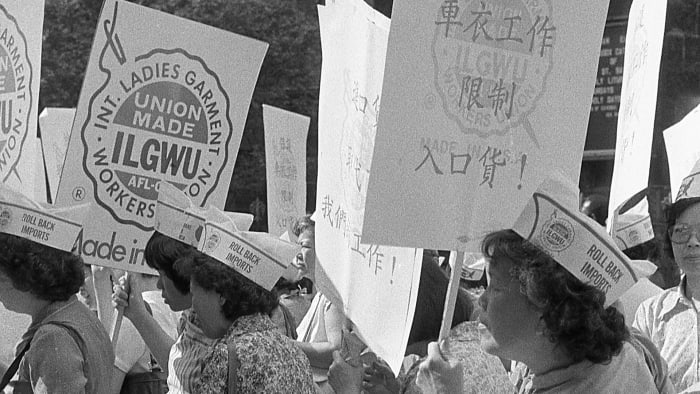 Garment workers with the ILGWU stand on the streets of Chinatown with protest signs in their hands.