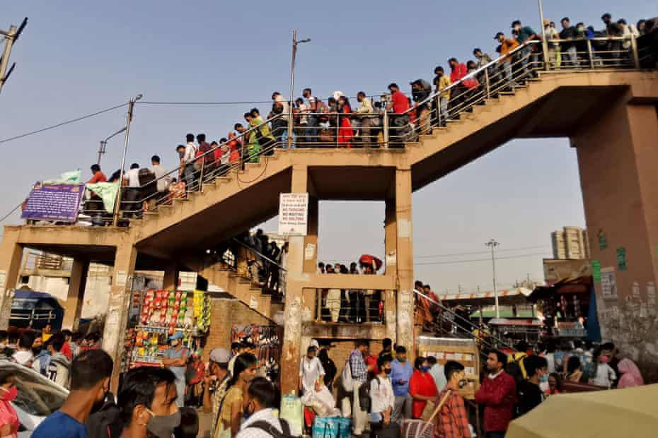 People crowd at a bus station to reach their native places hours before a week-long lockdown ordered by the Delhi government comes to effect in New Delhi on April 19