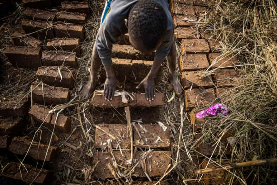 Ambrose, 11, who works at a brick-making site with his mother in Uganda. Child labour has risen steeply during the pandemic.