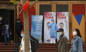"A medical worker adjusts her mask near propaganda boards showing famed Chinese medical expert Zhong Nanshan and the words ""Vaccine China Made"" outside vaccination center in Beijing Friday, April 9, 2021."