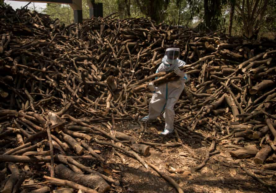 Cemetery workers wearing PPE kits (personal Protection Equipment) sort logs of wood for the funeral pyres to perform the last rites of the patients who died of the Covid-19 coronavirus disease on April 22, 2021 at a crematorium in the outskirts of New Delhi, India