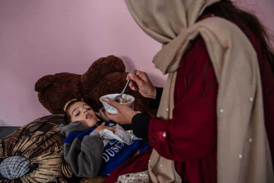 Tawab, 7, who was born with cerebral palsy, receives his lunch at the Fatima Khalil school in Kabul.
