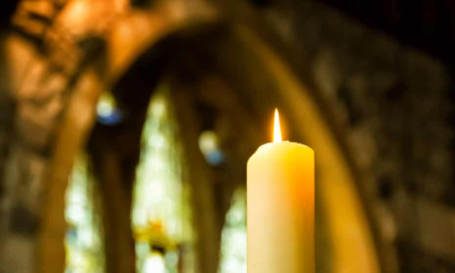 Church candle with stained glass window in the background