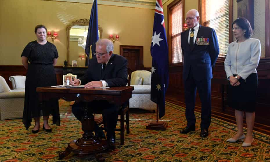 The Australian prime minister, Scott Morrison, signs a condolence book as his wife, Jenny, governor general David Hurley and his wife, Linda, look on.