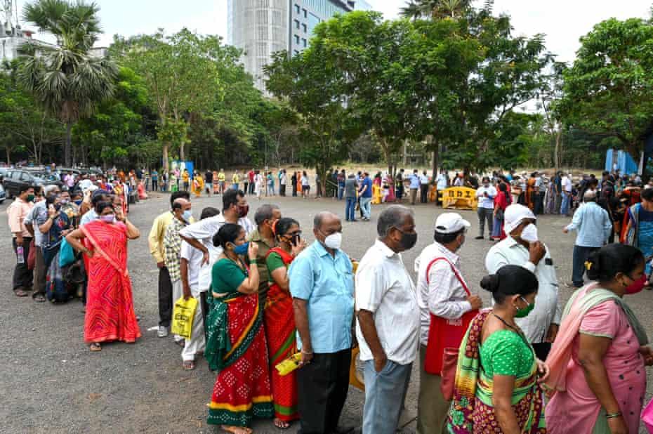 People wait in queues to receive the Covid-19 coronavirus vaccine at a vaccination centre in Mumbai 21 April