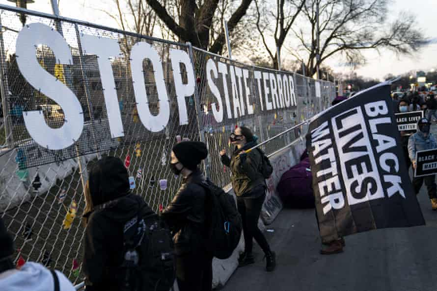 A sign reading 'stop state terror' hangs on a perimeter security fence as protest over the fatal shooting of Daunte Wright by a police officer continued on Saturday.