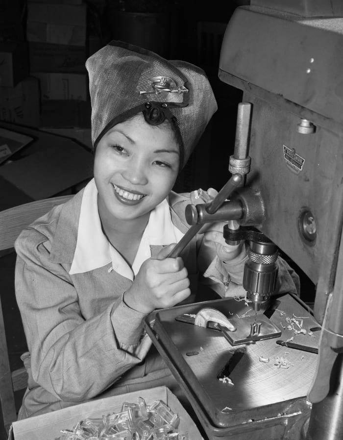 Sallie See Moi Choi, a Chinese American born in Honolulu who is participating in the war effort at a defense factory in Los Angeles.  She is pictured here operating a drill, 1943.