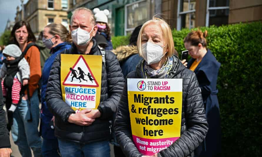 Protesters hold up placards as they block a immigration enforcement van, stopping it from leaving Kenmure Street in Glasgow.