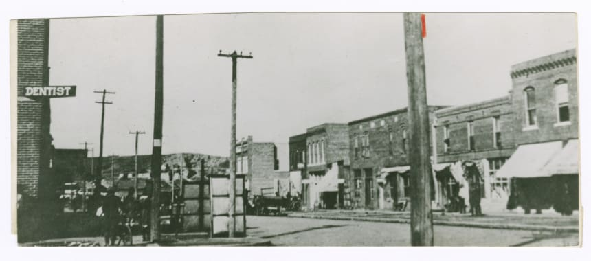 A black and white photograph of the Greenwood neighborhood of Tulsa, Oklahoma, before 1921. It shows storefronts, telephone wires, and a sign for a dentist's office.
