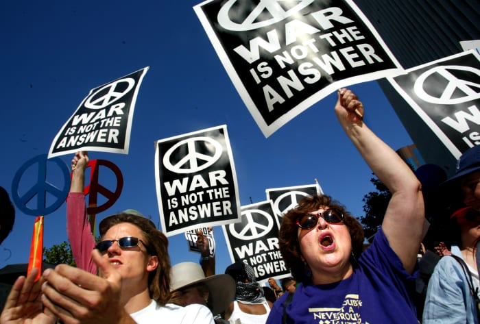 Joshua Besneatte, of Los Angeles, and Susan Robbins, right, of Irvine, take part in an anti-war protest at the Federal Building in Westwood, CaliforniaOctober 6, 2002. Over 4,000 people gathered to voice their opposition to a war against Iraq.