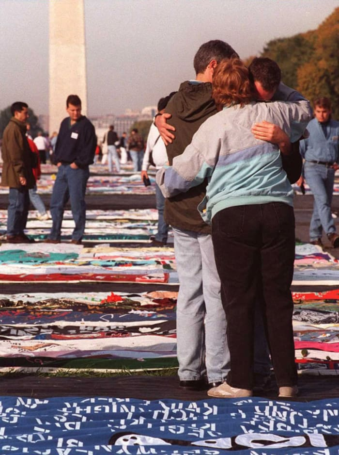 Three people take comfort in each other as thousands of friends and family of AIDS victims visit the AIDS Memorial Quilt displayed on the National Mall, Washington, DC on October 12, 1996.