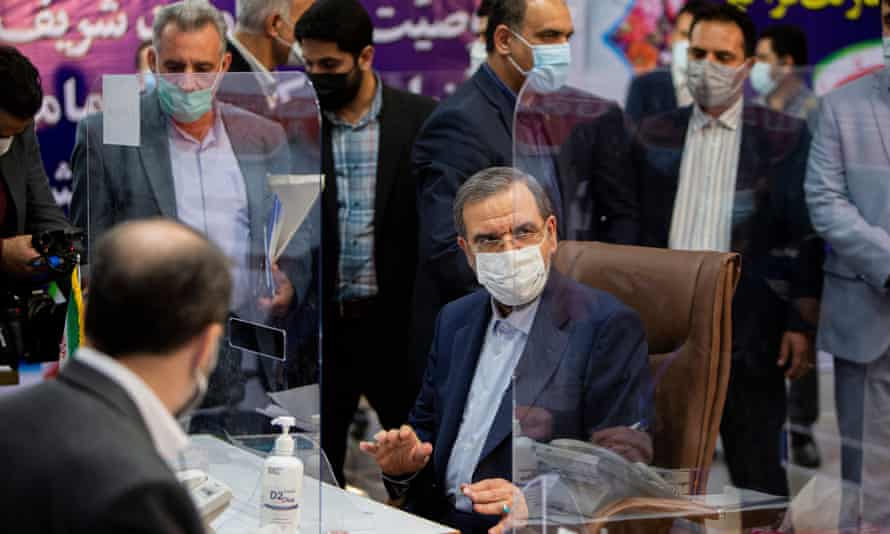 man in face mask sitting at a desk surrounded by other people in masks behind transparent partitions