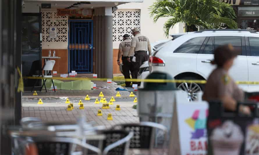Miami-Dade police investigate near shell case evidence markers on the ground where a mass shooting took place outside of a banquet hall early Sunday in Hialeah, Florida.