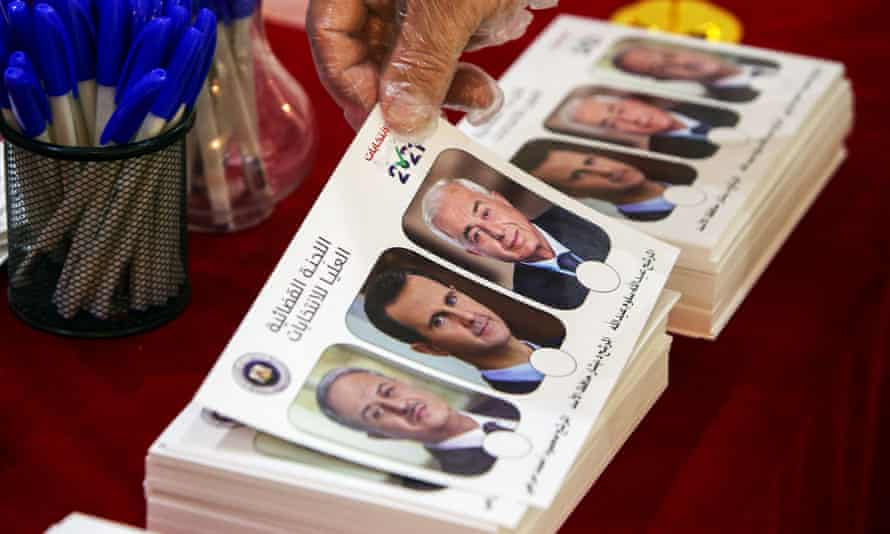 A Syrian national living in Kuwait picks up a ballot bearing the images of the three Syrian presidential candidates.