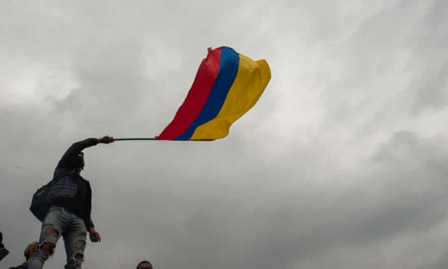 A demonstrator waves a Colombian flag in Bogotá on Monday.