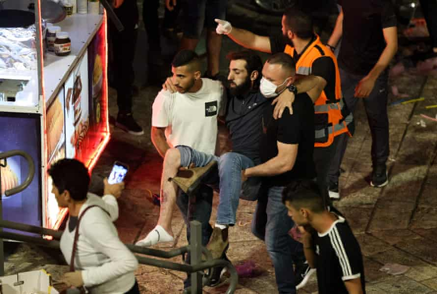 Palestinians assist a wounded man amid clashes with Israeli security forces outside the Damascus Gate in Jerusalem's Old City .