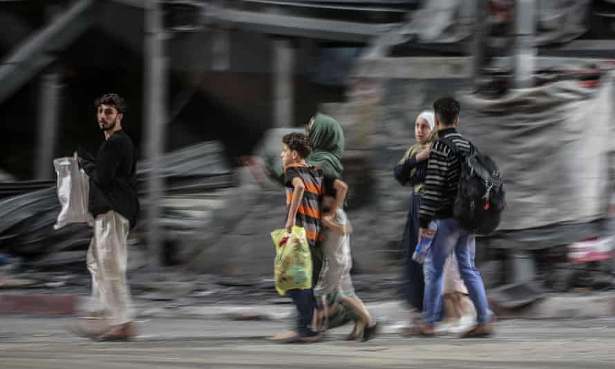 A Palestinian family flee from their house during Israeli airstrikes in the east of Gaza City early on Friday.
