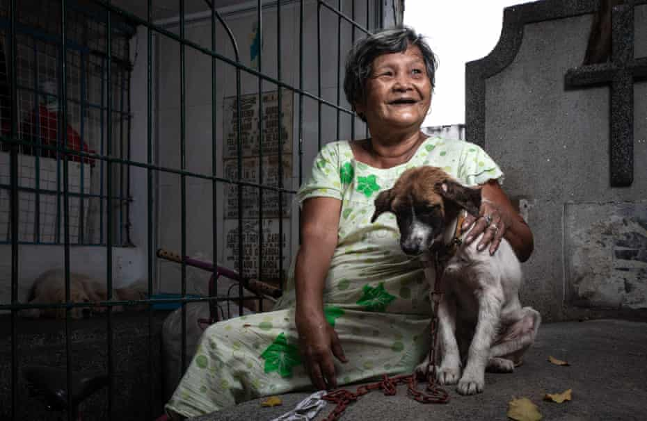 A woman with puppy on chain at the cemetery.