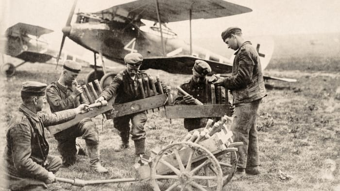 German soldiers loading gas cans onto military planes during World War I, c.  1915.