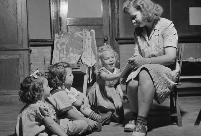 A woman reading a story to three young children at a child care center in New Britain, Connecticut.  Photographed by Gordon Parks for the Office of War Information, June 1943.