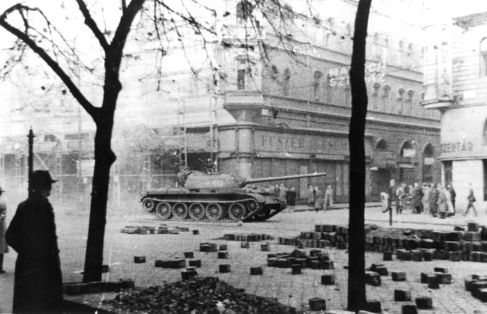 View of the Russian Army tank as it patrols past pedestrians during the Hungarian Revolution, Budapest, Hungary, November 1956.