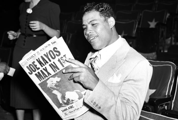 Joe Louis smiles while reading the NY Daily News the day after his fight with Schmeling on June 22, 1938.