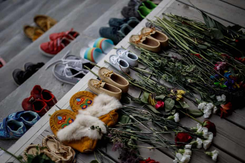 Flowers, shoes, and moccasins sit on the steps of the main entrance of the Mohawk Institute in Brantford, Ontario, to honor the children who died.