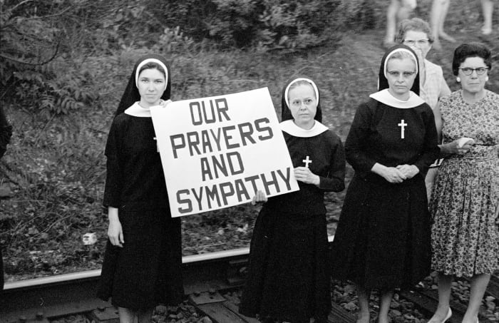 Catholic nuns and other mourners stand alongside railroad tracks as a 21-car train carries the body of Senator Robert F. Kennedy from New York to Washington, D.C. for burial in Arlington National Cemetery.
