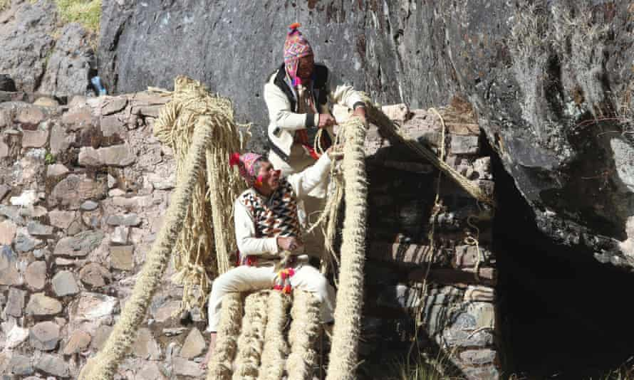 Members of the Huinchiri community use traditional weaving techniques to rebuilt the hanging bridge in Canas, Peru, 13 June 2021.