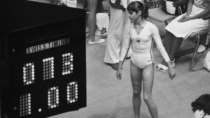Nadia Comaneci looks at the Olympic scoreboard showing her perfect score of 10.0, such as 1.00 because the computer and display facility were not equipped to handle what Nadia was going to do at the Olympic competition in gymnastic.