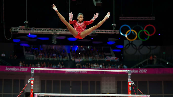 Gabrielle Douglas of the United States flew over the apparatus on uneven bars during the women's team gymnastics finals at North Greenwich Arena during the 2012 Summer Olympics in London, England on Tuesday July 31, 2012.