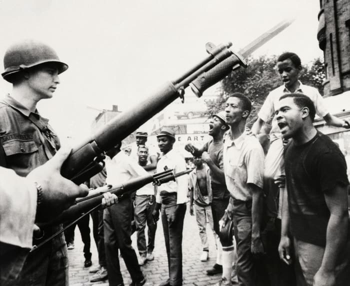 Newark, New Jersey, July 14, 1967: Black people laugh at National Guards wielding bayonets here on July 14.  The New Jersey State Police and National Guard were called in on July 14 to assist Newark Police after the second night of unrest in the largest New Jersey city.