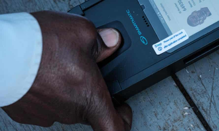A man puts his thumb on a biometric machine to check his ID to cast his vote at a polling station in Kampala, Uganda