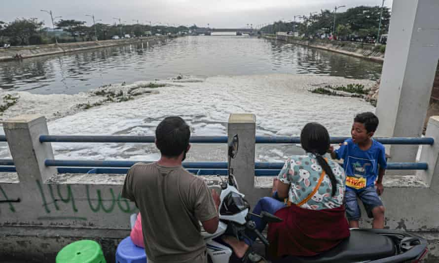 A family looks over the pollution spilling from the Marunda sluice bridge in Jakarta.