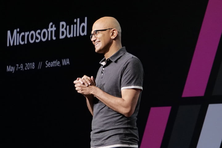 Microsoft CEO Satya Nadella standing onstage in a welcoming pose.